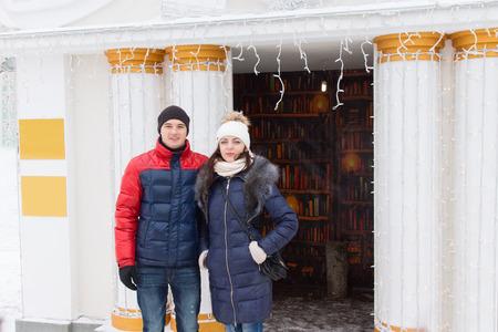 beanies: Joven pareja en ropa de invierno posando al aire libre delante de columnas blancas adornadas flanquean una entrada decorada con una guirnalda de peque�a fiesta o las luces de Navidad