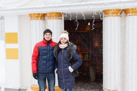 beanies: Young couple in winter clothes posing outdoors in front of ornate white columns flanking an entrance decorated with a garland of small party or Christmas lights