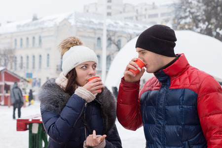 impermeable: Young couple in warm winter clothing, scarves and knitted caps standing sipping hot drinks in a wintry town square