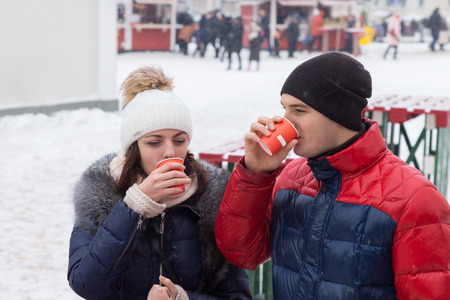 impermeable: Young couple standing outdoors in an urban square in winter snow sipping hot drinks on a cold day from takeaway cups, people walking in the distance