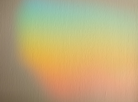 Soft blurred rainbow effect background with applied texture in muted pastel colors of the spectrum for a dreamy spiritual background
