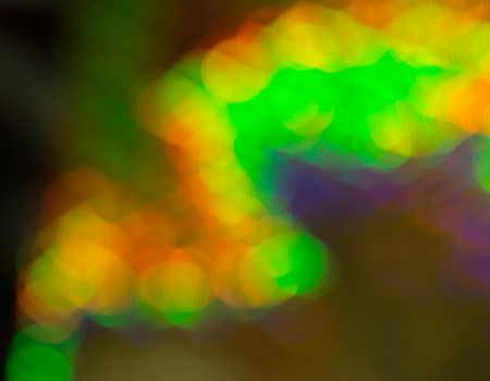 soft diffused light: Bright vibrant abstract bokeh background pattern and texture in green, yellow and orange with a dynamic zigzag shape for a festive design Stock Photo