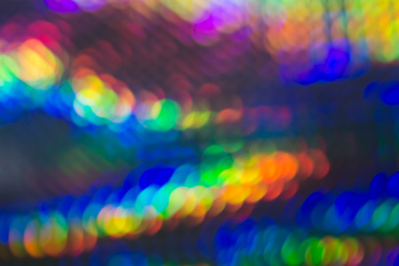 Vibrant abstract background with bokeh and motion blur in the colors of the rainbow with two converging lines of muticolored light for a festive design