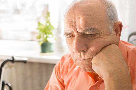 ansiedad: Cierre de mayor serio Hombre calvo, en camisa naranja, Mirar hacia abajo con el pu�o en el rostro Foto de archivo