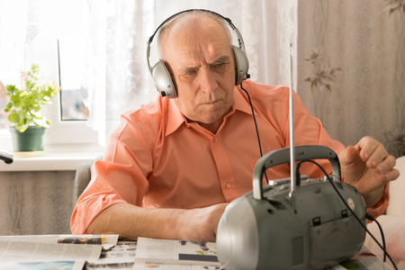 Close up Serious Senior Man Listening News at the Cassette Player Seriously White Sitting at the Living Room with Newspapers. photo