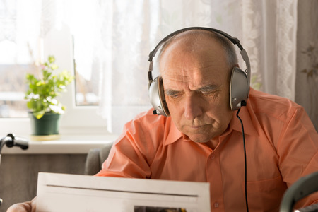 sombre: Serious Old Man with Headset Device Reading Newspaper Inside his Home. Stock Photo
