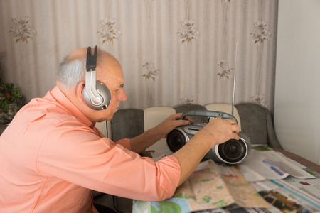 radio active: Sitting Elderly Listening at the Radio with Headset at the Table Inside his House.