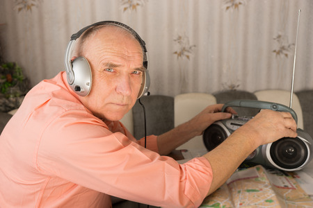 radio active: Close up Bald Elderly Listening Music at the Cassette Player with Headset While Looking at Camera. Stock Photo