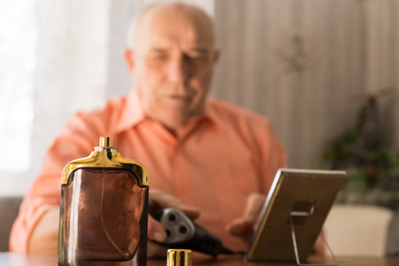 aftershave: Close up Brown Aftershave Bottle on a Table In Front Old Bald Man with Razor and Mirror. Stock Photo