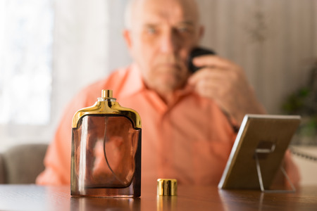 aftershave: Close up Open Aftershave Bottle on a Table In front Old Man Shaving his Beard with Razor and Small Mirror.