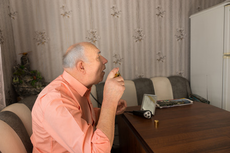 aftershave: Close up Side View of Old Bald Man Spraying Aftershave on his Face After Cleaning his Beard While Sitting at the Sofa Inside the House. Stock Photo
