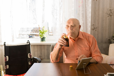 aftershave: Close up Sitting Old Bald Man in orange Shirt Holding a Bottle Spray of Aftershave after Cleaning his Face at the Living Room. Stock Photo
