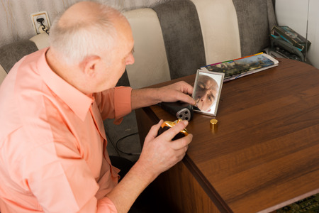 aftershave: Close up Sitting Old Bald Man with Aftershave Bottle on his Hand Looking at the Small Mirror on Wooden Table.