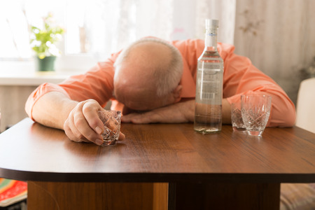 depressed man: Close up Drunk Old Bald Man Leaning on the Wooden Table with Vodka Holding a Small Glass Stock Photo