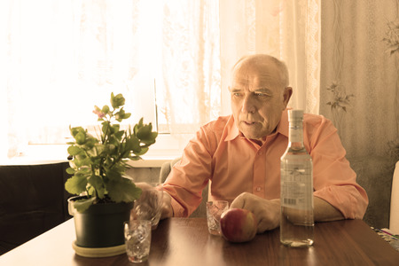 downhearted: Old Bald Drinking Man Looking at Green Plant on as Pot Placed on the Wooden Table with Apple, Shot Glasses and Vodka Bottle.