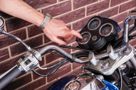readout: Close up of Young Man Closely Examining Dial Gauges on Motorcycle Consol