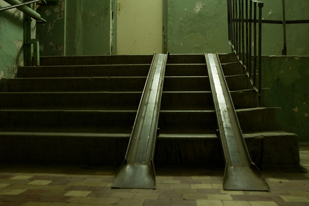 concrete steps: Two metal ramps overlaying a flight of concrete steps to allow for loading and access for vehicles or wheelchairs