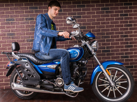 suave: Attractive Young Man in Casual Jacket and Jeans Outfit on his Blue Motorbike at Home with Brick Wall Background.