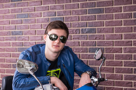 handlebars: Trendy young man on a motorbike leaning over the handlebars in his fashionable sunglasses to smile at the camera Stock Photo