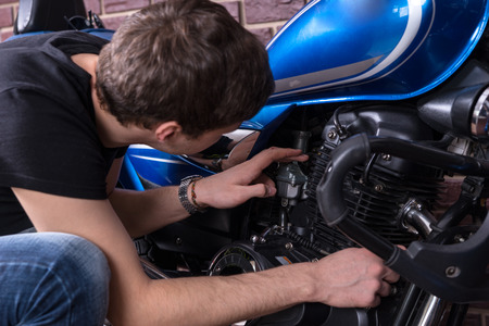 view from behind: Young man bending down checking out his motorbike engine, close up view from behind Stock Photo