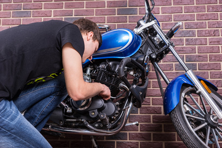 Hombre joven que trabaja en su encargo azul de la motocicleta mientras que mira algunas piezas de cerca. Capturado en frente de la casa Pared de ladrillos. Foto de archivo