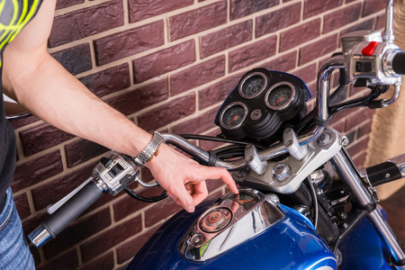 readout: Close Up of Young Man Examining Gas Gauge on Tank of Blue Motorcycle Stock Photo