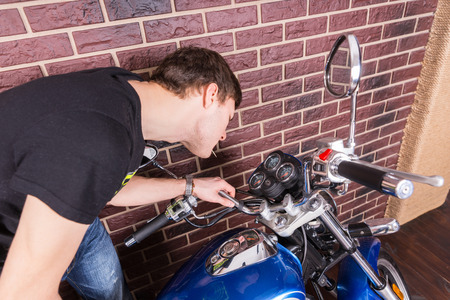 gauges: Young Man Closely Examining Analog Gauges on Classis Motorcycle Console