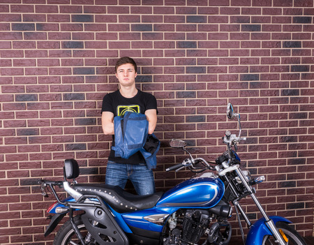 self assured: Gorgeous Young Man Holding his Jacket While Standing Behind his Sports Motorcycle, In Front of a Brick Wall, While Looking at the Camera