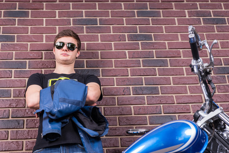 suave: Attractive Young Man in Shades Holding his Jacket Behind his Motorbike on a Brick Wall Background.