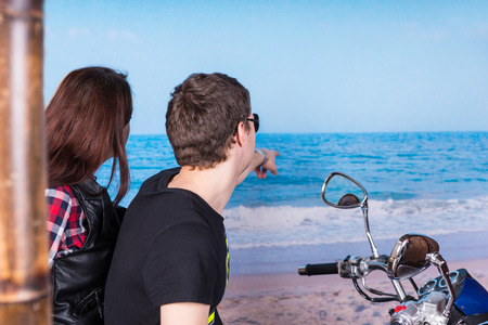 sweethearts: Close up Young Sweethearts on a Motorcycle Taking a Break at the Beach While Looking at the Beautiful Ocean. Stock Photo