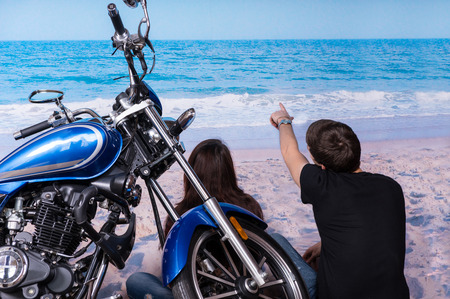 Young Couple with Motorbike Sitting on White Sand at the Beach While Looking at the Tranquil Ocean on a Tropical Climate. Stock Photo
