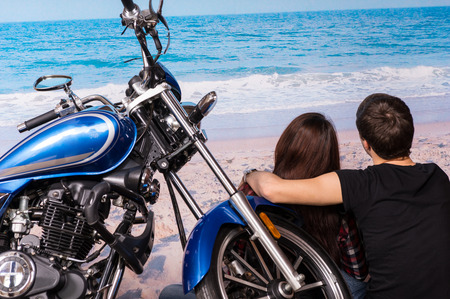 tryst: Young Romantic Couple Sitting with Arms Around Each Other on Sandy Beach with Motorcycle Stock Photo