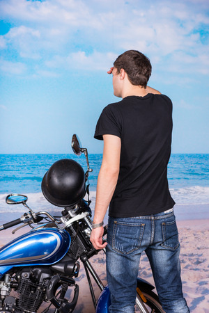 Rear View of Young Man Looking into the Distance and Standing next to Classic Blue Motorcycle on Beach