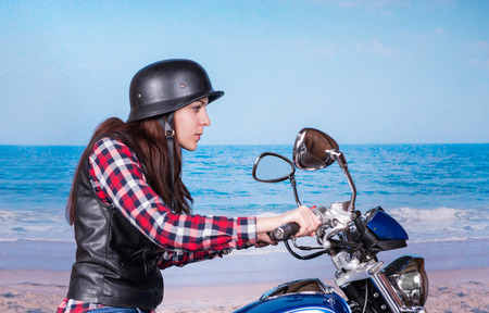 tough woman: Profile View of Tough Young Woman Wearing Helmet Riding Past Beach on Motorcycle