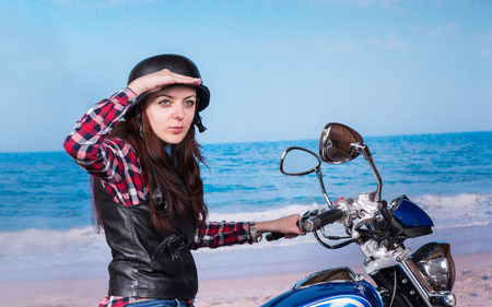 Young Woman Wearing Helmet Sitting on Motorcycle at Beach and Looking into the Distance photo