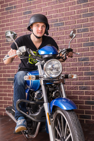 imagining: Young Man Wearing Helmet Sitting on Blue Motorcycle in front of Interior Brick Wall Looking as if Imagining the Ride