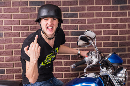 intolerant: Rude aggressive young man sitting on his motorbike in his helmet making a rude insulting gesture with his middle finger while shouting at the camera Stock Photo