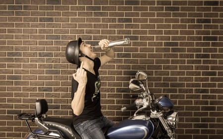 vindictive: Faded retro image of a hyped up young motorcyclist in an old-fashioned helmet sitting on his motorbike drinking alcohol directly from the bottle and punching the air with his fist Stock Photo