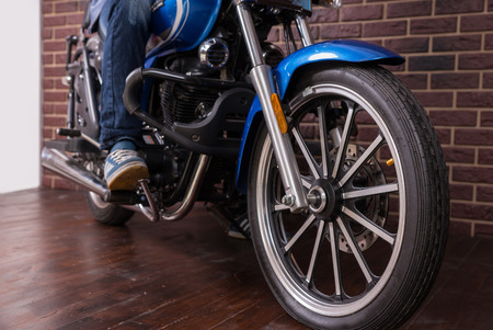 wheel house: Man Riding a Blue Sports Motorbike on the House Wooden Floor, Emphasizing the Wheel in Close up.