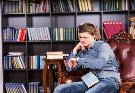 unsettled: Serious Young Guy in Trendy Fashion Sitting and Waiting at Library Chair with a Book, Looking at his Wristwatch Stock Photo