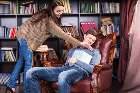 Librarian trying to wake a sleeping man who has dozed off in an armchair in the library tapping him on the cheek