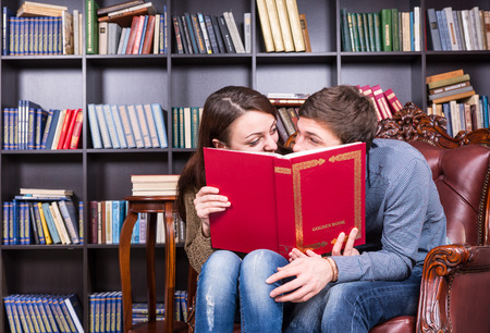 camaraderie: Young Sweet Couple Sitting at the Library Chair While Hiding Behind a Red Book and Looking Each Other So Closed.