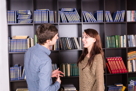 tomes: Half Body Shot of a Happy Young Couple Talking Inside the Mini Library While Facing Each Other.