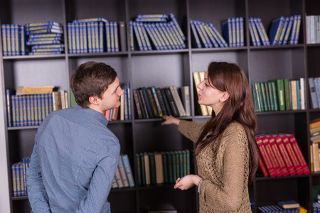 tomes: Sweet Young Couple Standing While Talking Beside Bookshelves at the Library