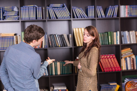casual attire: Serious Young Couple in Casual Attire Talking Inside the Mini Library Near the Bookshelves.