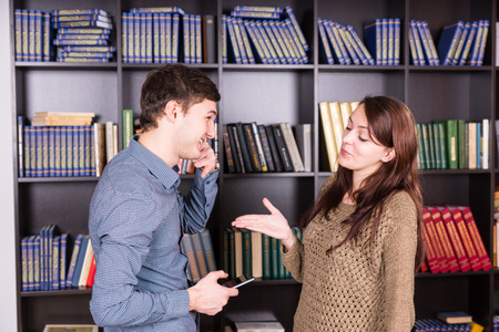 half body: Half Body Shot of Happy Young Lovers Discussing Inside the Library In Front of the Bookshelves. Stock Photo