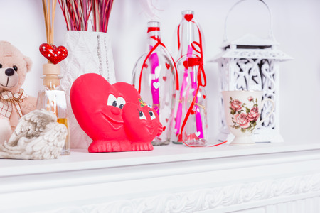 giftwrapped: Valentines Day Heart Figurine Amongst Other Decorations on White Fireplace Mantle Stock Photo