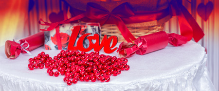 themed: Red Beads and Crackers on Love Themed Table Decorated for Wedding or for Valentines Day