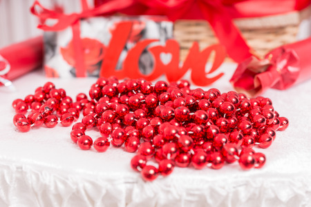 giftwrapped: Decoration of red beads arranged on a white tablecloth with a red cutout of the word - Love - at a wedding reception