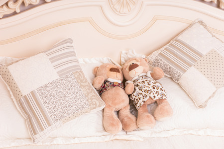 snuggling: Male and Female Teddy Bear Couple Snuggling Amongst Cushions on Bed